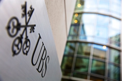 A logo sits on a sign outside a UBS AG bank branch in Lausanne, Switzerland, on Monday, Oct. 21, 2013. Photographer: Gianluca Colla/Bloomberg